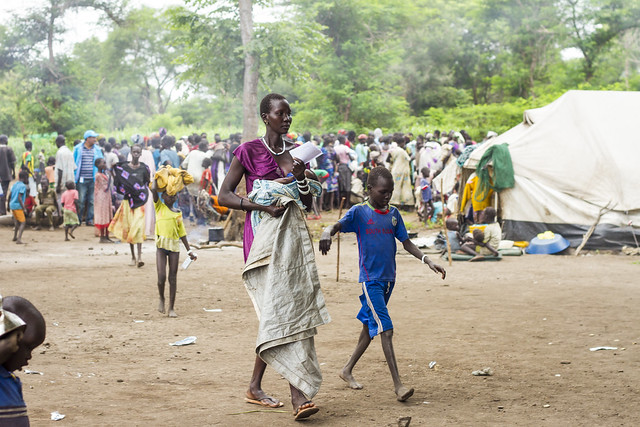 A mother walks back to her temporary shelter after visiting a clinic