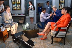 A technician adjusts a microphone on U.S. Secretary of State John Kerry before he and U.S. Commerce Secretary Penny Pritzker sit for a joint television interview with NDTV host Prannoy Roy between meetings during the U.S.-India Strategic & Economic Dialogue on July 31, 2014. [State Department photo/ Public Domain]