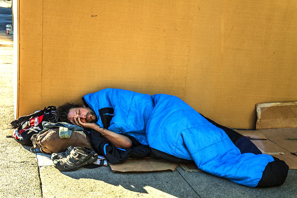 Man-on-sidewalk-in-blue-sleeping-bag-in-front-of-yellow-wall--Portland
