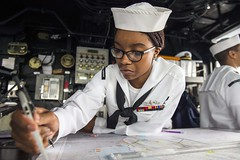 A Sailor plots a course on the bridge of USS Comstock.