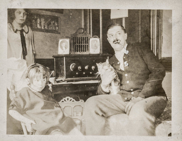 A Man With A Cat And Cigar Sits Next To A Girl Wearing Hea