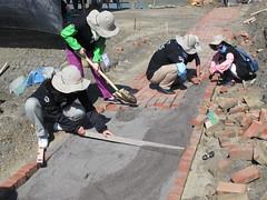志工以長木板推平砂石。南布袋濕地鱟生態復育池工作假期,鋪設紅磚步道