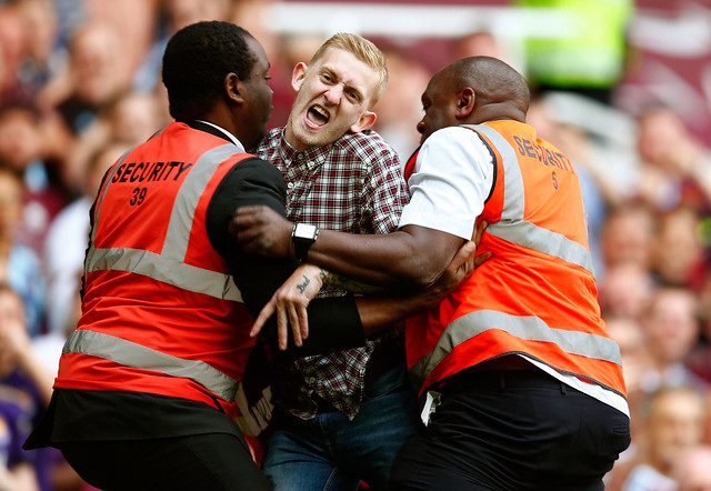 Pitch Invader being held by security