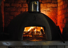 kitchen appliance(0.0), masonry oven(1.0), wood-burning stove(1.0), fireplace(1.0), fire(1.0), iron(1.0), darkness(1.0), hearth(1.0),