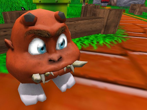 Image Description: Head with big, jagged teeth and legs standing to one side of a red brick path.