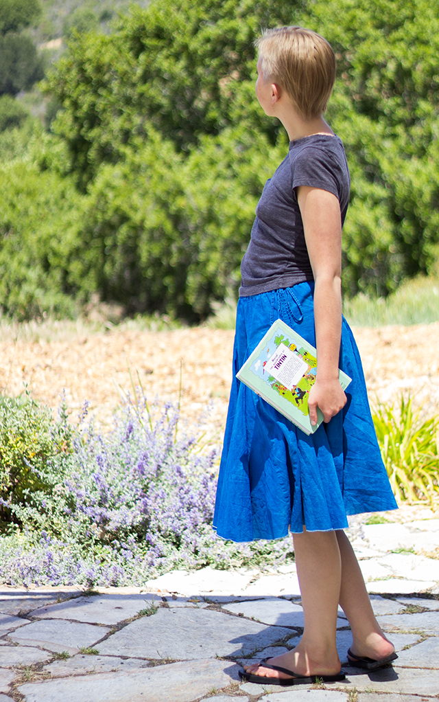 cropped grey t-shirt, full royal blue skirt, mint volume of The Adventures of Tintin by Herge