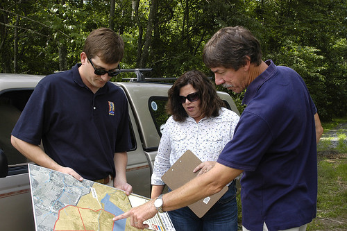 Mike Liskey, right, refers to a site map while discussing ongoing conservation projects with Chase Milner, with the foundation, and Amy Roscher, with the Virginia Farming television program. NRCS photo.