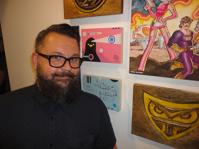 Robbie Perchaluk beside illustrations at Hashtag Art Gallery in Toronto