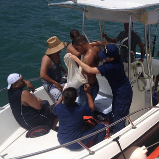 Petty Officers 3rd Class Maritza Morgan and Brandywine Hightower, Sector San Juan Health Service personnel, place the arm of an injured boating passenger in a splint June 9, 2014, before transferring the man to local Emergency Medical Service personnel at Coast Guard Sector San Juan for transport to a local hospital. The passenger was with six other people transiting aboard a 19-foot-recreational power boat, approximately one nautical mile off Fort San Felipe del Morro in San Juan, Puerto Rico, when he reportedly injured his wrist after losing his balance and falling on the bow of the boat. (Coast Guard photo by Master Chief Petty Officer Robert Gonzales, Boat Station San Juan officer in charge)
