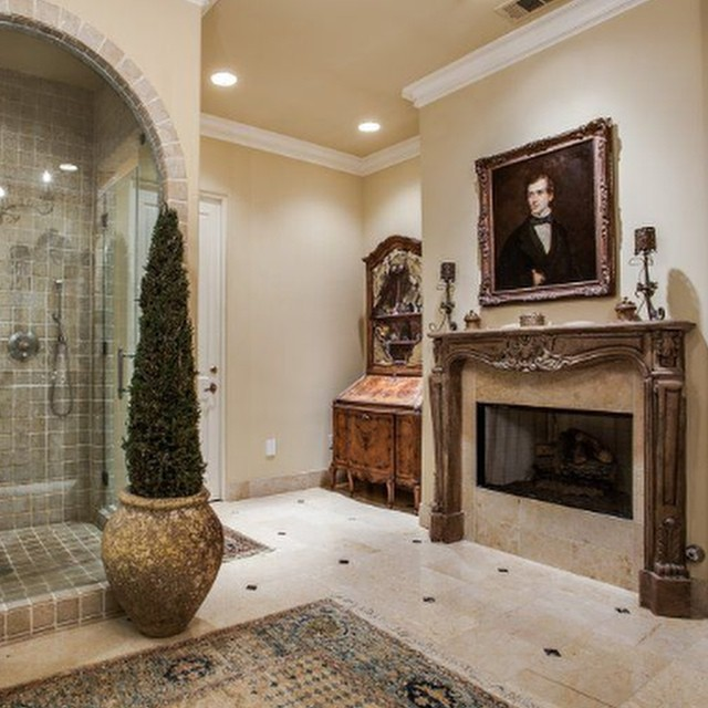 Hand carved limestone fireplace in a lavish master bath