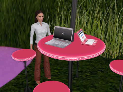 Image Description: Eve standing behind a bright pink table upon which two laptops sit.
