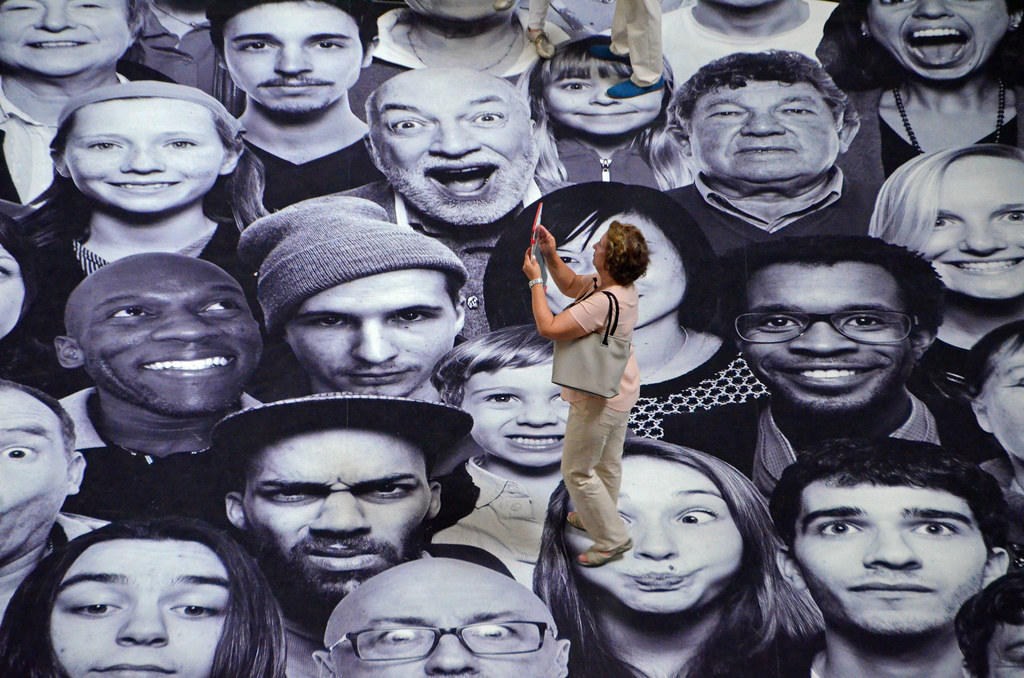 Woman taking a photo among the faces