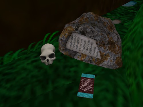 Image Description: Skull and Gravestone with alien lettering on it; there is a pamphlet in front of both.