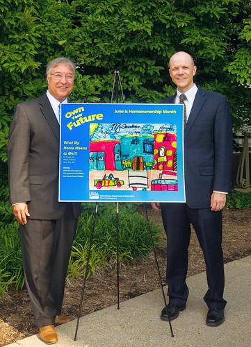 Tony Hernandez, Administrator for USDA Housing Programs, and Doug O'Brien, Deputy Under Secretary for Rural Development, display the winning poster that will be displayed in the Secretary of Agriculture's office.