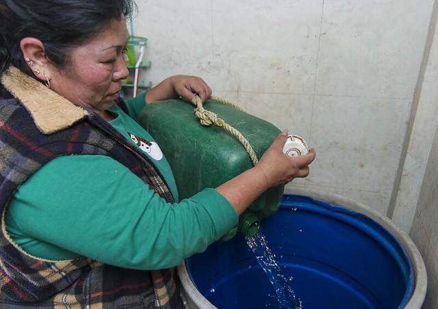 Foto: AFP - A mexicana Defina Salinas despeja água coletada da chuva em balde para usar em sua casa, na Cidade do México.