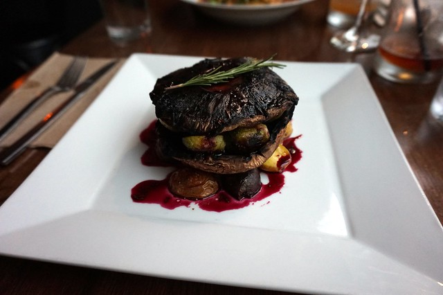 Portobello steak with brussels sprouts and roasted potatoes in a beet reduction