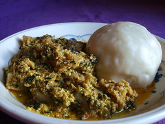 A shallow bowl on a purple tablecloth.  It contains a stew of meat and spinach, thickened with coarsely-ground seeds, and a lump of pounded yam.