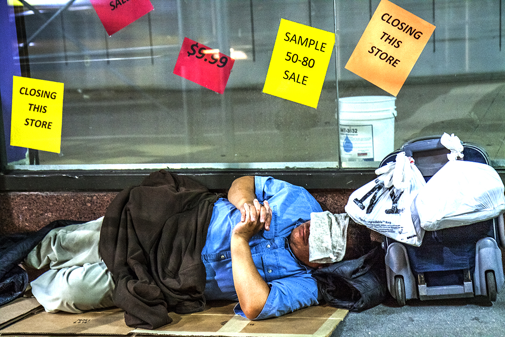 Man-sleeping-in-front-of-closed-store-near-Times-Square-in-7-14--New-York