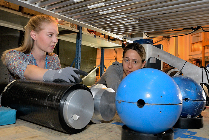 Los Alamos National Laboratory postdoctoral researcher Elena Guardincerri (r) and undergraduate research assistant Shelby Fellows (l) prepare a lead hemisphere inside a muon tomography machine.