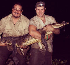Murray and Sasa pose with a restrained crocodile after a capture.