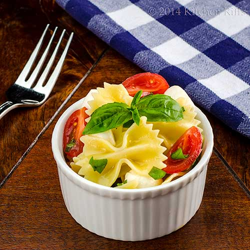 Pasta Caprese in ramekin with basil garnish