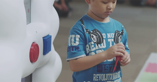 남자아이가 기계 앞에서 출력된 공룡 모형을 만지고 있다.