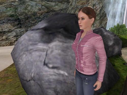 Image Description: A woman standing by a large rock.