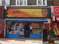 "A terraced shopfront with a sign above reading ""Julia knows beauty / cosmetics & human hair / TEL: 0208 686 8890"".  The background of the sign is coloured yellow and orange, and there's a headshot of a young brown-skinned woman on the right-hand side."