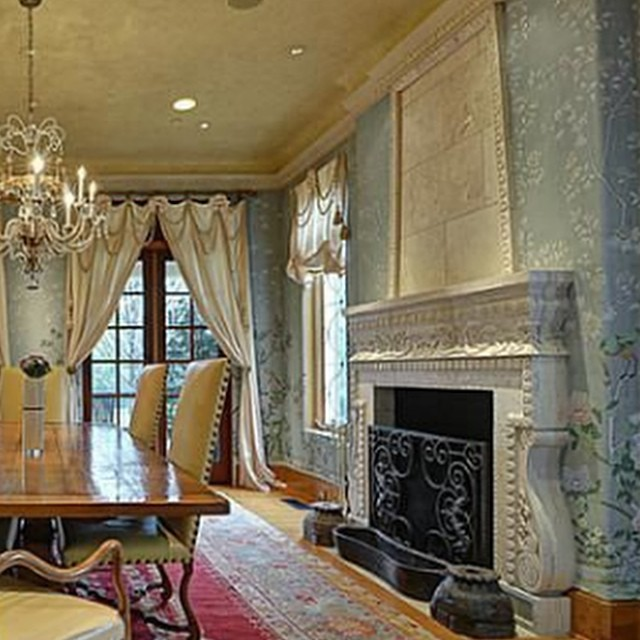 Dining room with lavish details, custom wall art, hand carved fireplace