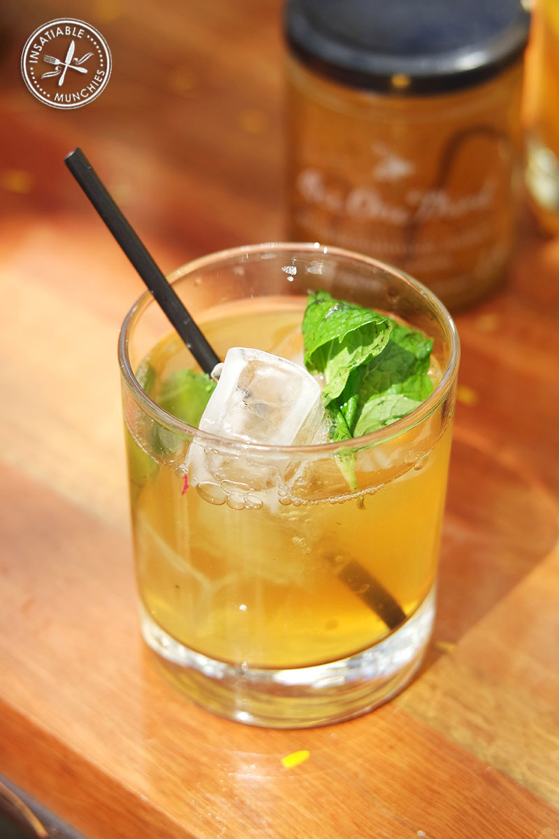 A cold glass of lemon, honey and mint iced tea.