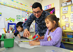 A Sailor participates in a math exercise during a community relations event at Sullivan's Elementary School.