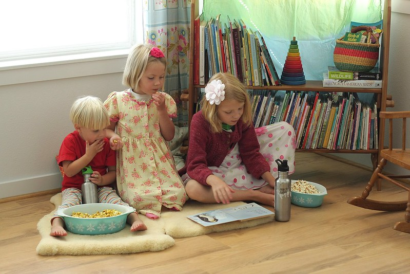 K reading to her siblings (with popcorn!)