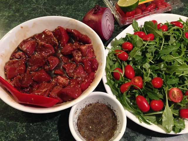 Marinating beef with a plate full of arugula and tomatoes.