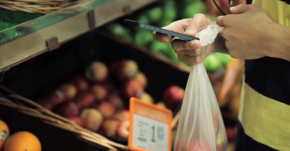 MySmartEye 사용자가 마트에서 애플리케이션으로 사진을 찍어서 자원봉사자에게 보내어 과일을 고르고 있다.