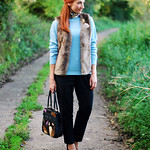 Faux fur gilet, blue sweater and black tailored trousers