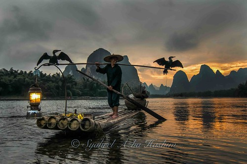 china travel sunset mountains detail birds clouds cormorants fishing fisherman nikon colorful guilin getaway unique traditional naturallight bamboo handheld lantern dramaticsky iconic conventional bambooraft d300s syahrel