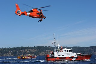 Petty Officer 2nd Class Ryan Carr, an aviation survival technician assigned to U.S. Coast Guard Air Station Port Angeles, Wash., is lowered from an MH-65 Dolphin helicopter onto the deck of Canadian Coast Guard Ship Cape Naden, a 47-foot motor lifeboat from Sidney, British Columbia, during a training exercise in Moresby Passage, Aug. 7, 2014. Once aboard, Carr instructed crewmembers on the proper techniques for tending a trail line and completing helicopter hoists. U.S. Coast Guard photo by Petty Officer 3rd Class Katelyn Shearer.