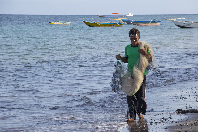 A fisherman carries his net along the shore in Atauro, Timor-Leste. Photo by Holly Holmes, 2013