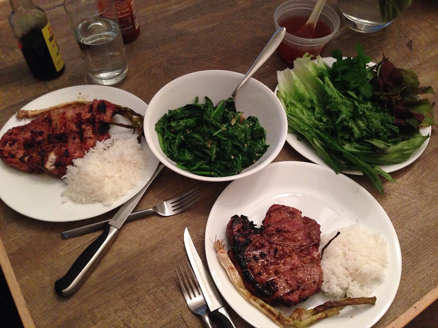 Dinner table with grilled pork chops, rice, mustard greens, and fresh herbs