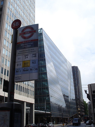 """Slanty buildings with lots of windows, and a bus stop sign reading """"Westminster City Hall towards Marble Arch, Pimlico or Sloane Square""""."""