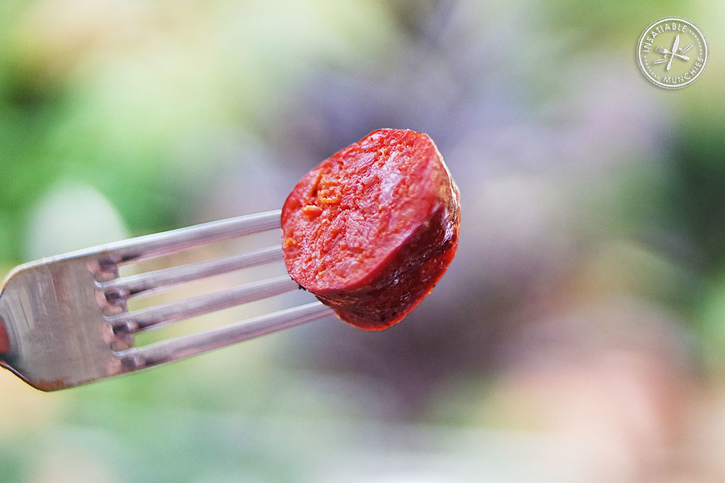 Chorizo is barbecued in a smoker and then sliced. In this photo, a piece of chorizo is speared on the end of a fork.