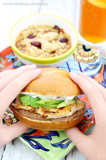 Grilled Chicken Tortas, Mexcian Chicken & Rice Soup and Mango Sweet Tea. Torta being held in hand.