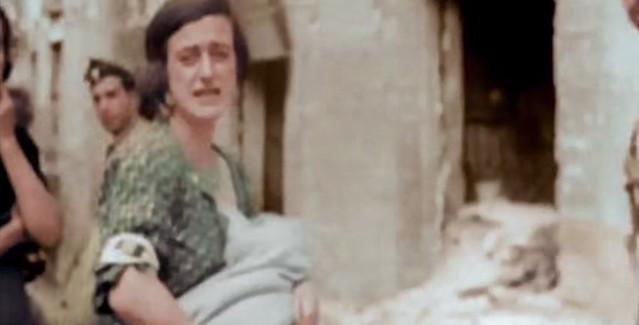 Una mujer llora con su hijo en brazos junto al Alcázar durante el asedio. Captura de un vídeo real a color de la Guerra Civil en Toledo en el verano de 1936
