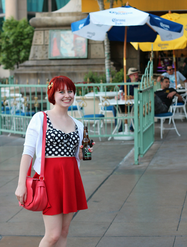 Las Vegas Outfit with a Polka Dot Top, Red Skater Skirt, and White Cardigan