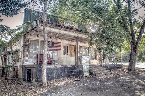 old trees usa building abandoned architecture rural vintage georgia store nikon closed unitedstates antique decay flag south country rusty americanflag architectural gasstation business southern faded adobe weathered boardedup generalstore frontporch derelict mica shady decayed smalltown gaspump outofbusiness lightroom countrystore fillingstation cherokeecounty ballground stancilsstore d7000 stgrundy