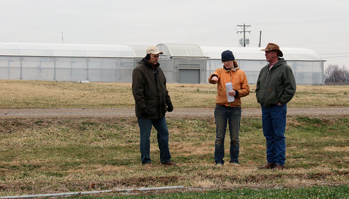 The University of Kentucky is using a Conservation Innovation Grant to improve the efficiency of seasonal high tunnels. NRCS and UK staff  view a water line with a high tunnel in the background. NRCS photo.