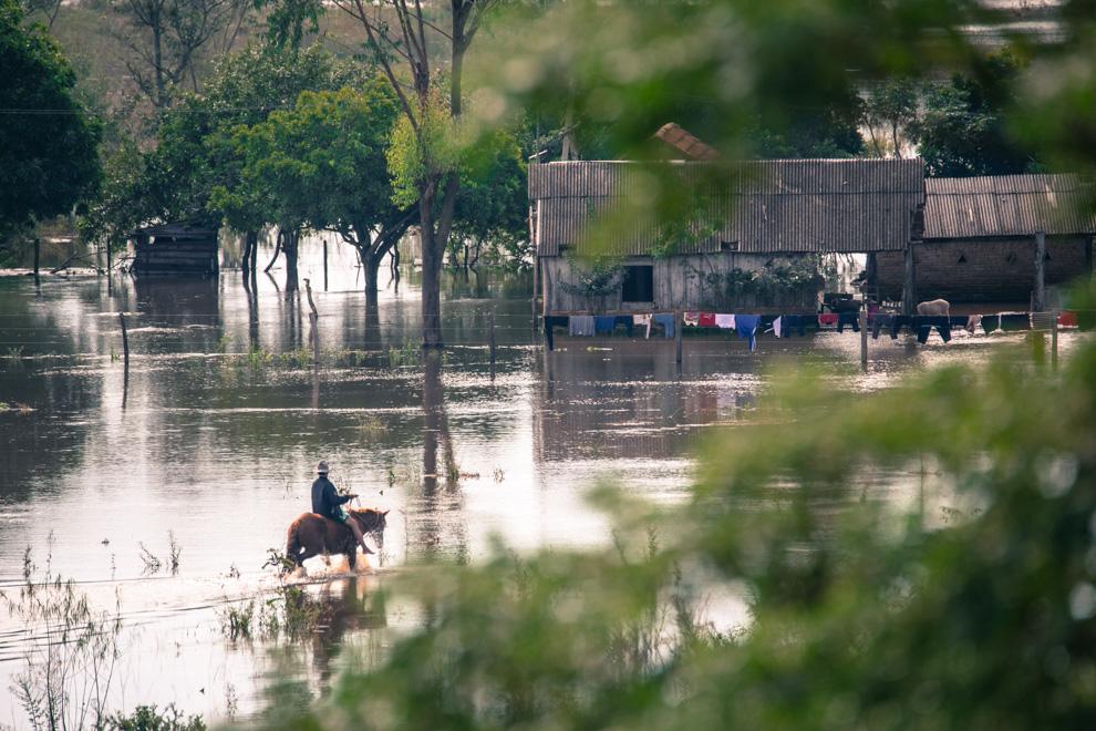 Un vecino del pequeño poblado de Puerto La Niña, en San Pedro, recorre a caballo rumbo a su domicilio inundado para recuperar muebles y pertenencias.(Tetsu Espósito)