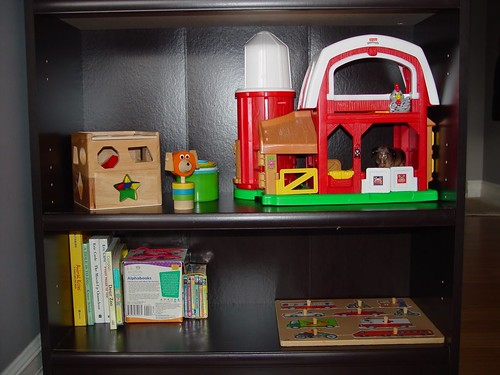 Child's toys neatly arranged on low shelves in the family's living room. (Photo from The Montessori Child at Home)