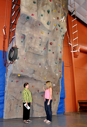 A climbing wall at Rimrock Trails Adolescent Treatment Services is one of many tools available to help troubled teens build their self-esteem. Pictured are State Director Vicki Walker (left) and Rimrock Trails' Residential Mental Health Counselor Courtney Parchmon.  Rimrock Trails employs 30 professionals dedicated to helping some of our most vulnerable adolescents.