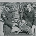 Lt. Colonel Ferguson congratulates 'Anzac' on being promoted to Corporal. Sgt R. Wilson was the mascot's handler